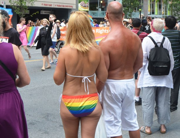 a woman with a rainbow string bikini stands beside a well tanned man in white shorts and no shirt as they watch women marching in the Dyke March