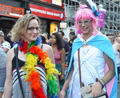 a couple in a parade, one has a rainbow coloured boa and the other has a pink wig and is draped in the pink and blue trans flag.