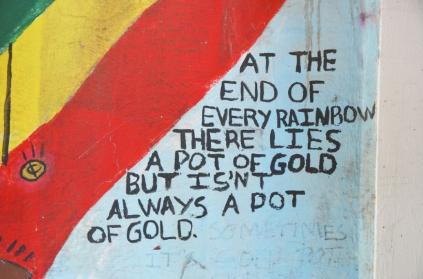 words written in black beside a red and yellow stripe, At the end of every rainbow there lies a pot of gold but isn't always a pot of gold.