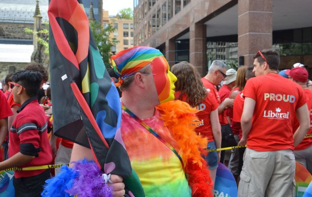 a man wearing a rainbow coloured mask and a rainbow bandana over his head, holding a flag. In the background is a group of people wearing red T-shirts that say Proud Liberal