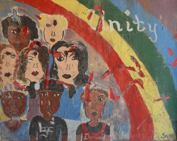 old mural that is not in good shape, a rainbow in the top right corner with the word unity written on it. A number of faces in the rest of the mural, men and women, different colours.