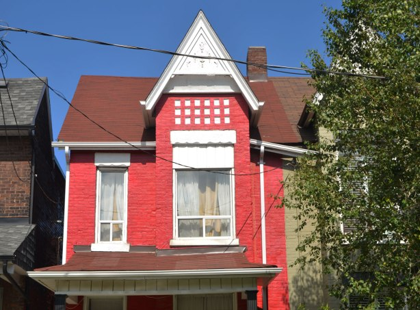 the top part of an old Victorian brick 2 storey house, painted red with white trim