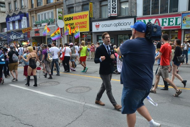 walkers in a dyke march in Toronto - a CTV reporter is walking backwards as he is being filmed following the Dyke March