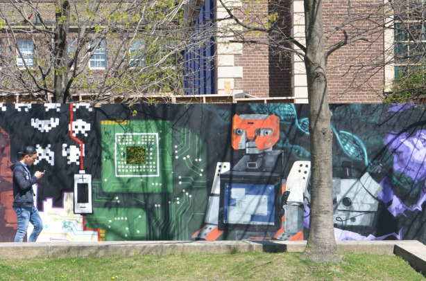part of a mural on an artwall on hoardings around a construction site for a new engineering building at the University of Toronto, a robot cat