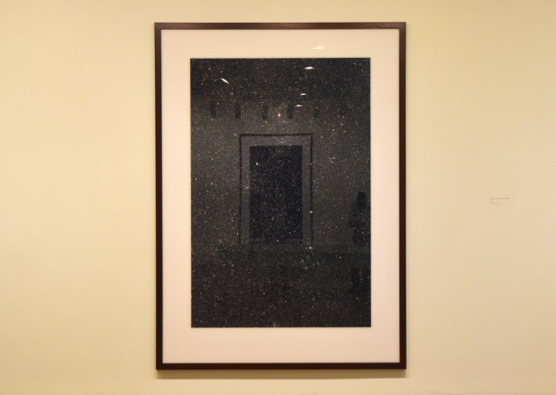 large photograph of the night sky, lots of stars and blackness. The black acts like a mirror and parts of the gallery are reflected in the picture.