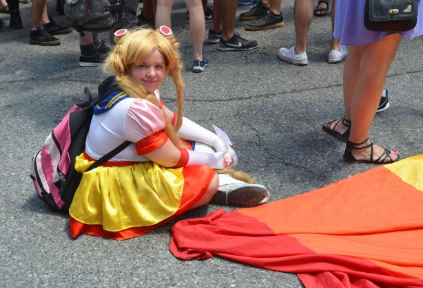 A woman dressed in a Sailor Moon costume sits on the ground beside a large rainbow flag