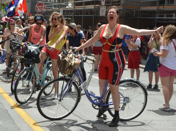 walkers in a dyke march in Toronto - one cyclist in a tight red body suit is yelling in celebration, other cyclists around her