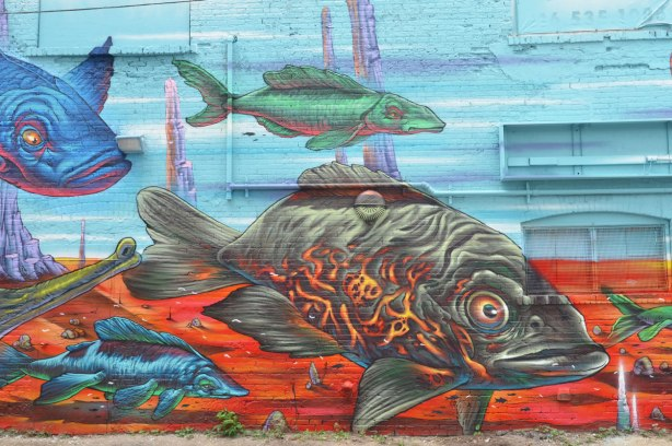 part of a mural by Bruno Smoky across the back of a large building, marine life, lots of fish in blues and greens as well as a small wood boat with a little white cabin on it.