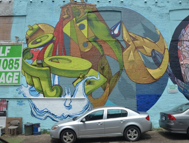 round mural painted by Sermob, car parked in front of it, stylized figures on water