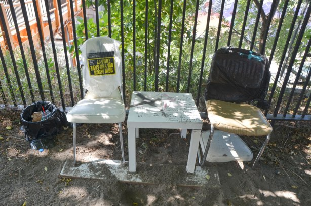 In a veryshady spot, against a metal fence, two old chairs with a white table between them, a sign on the table and a small garbage can to the left.