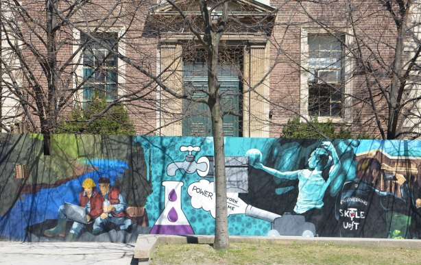 part of a mural on an artwall on hoardings around a construction site for a new engineering building at the University of Toronto, an older building behind, a volleyball player on the mural as well as two students sitting on the ground and looking at a laptop