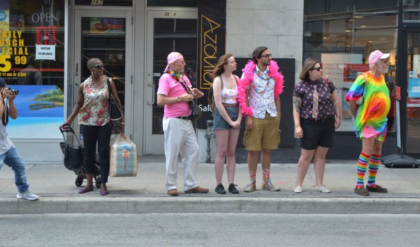 spectators on the sidewalk watching a parade. A man with a camera, a woman with her shopping, a man with a pink boa, another man with a pink shirt and white pants