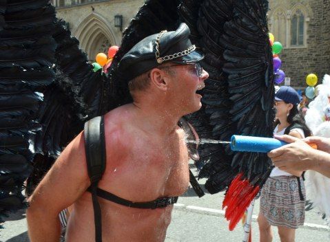 a man wearing black feather wings and a black leather cap is being sprayed with water