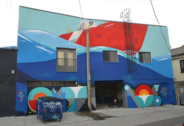 large mural by Peru on the back of a two storey building, a large red ship called the S.S. One Love in the water