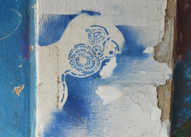 stencil in blue on concrete of a stylized face with big mouth made of a spiral of little shapes