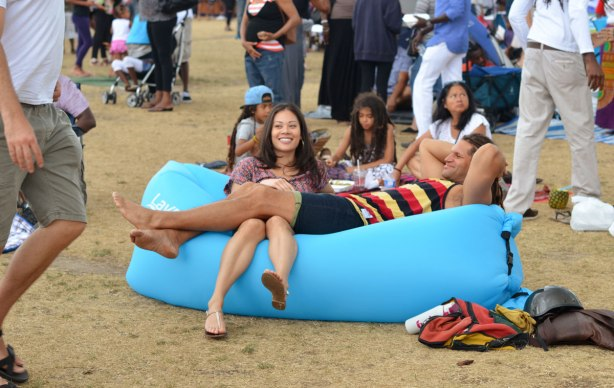a couple are lounging on a large light blue foamy thing, amongst a crowd at an outdoor music festival