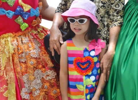 a girl in pink sun hat, white sunglasses and a bright multi coloured dress poses for a picture