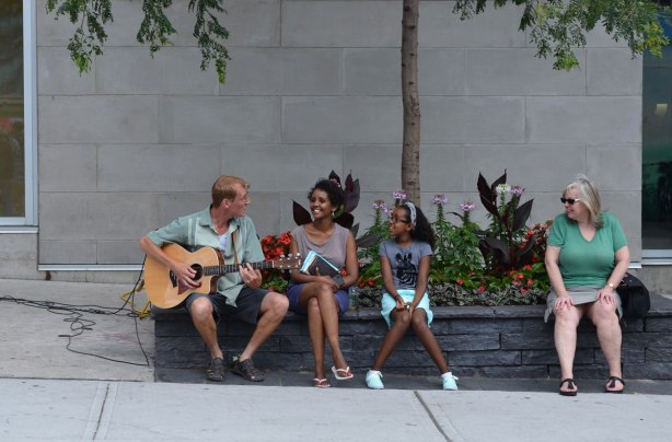 a young man plays a guitar for a mother and daughter, sitting on the edge of a planter outside. Another woman is watching