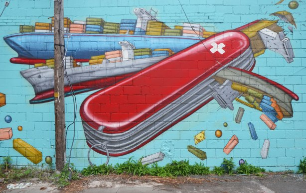 mural of a large red Swiss army knife that opens up to reveal container ships, not knife blades. The containers are falling off into the water.