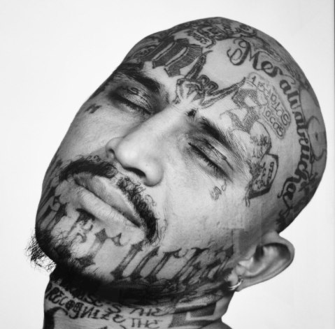 photo of a picture in a museum of a man's face that has been tattooed with gang symbols and words,