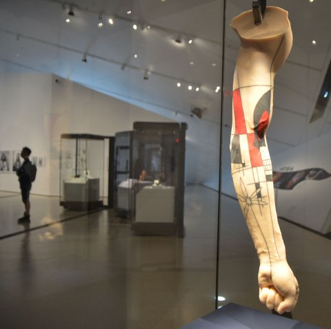 a silicone arm has been tattooed with a design that looks something like a cross between Frank Lloyd Wright and Mondrian. It is in a glass showcase in a museum.