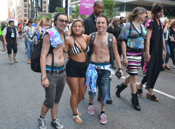 three people stop to pose for a photo as they walk in a trans parade for pride weekend