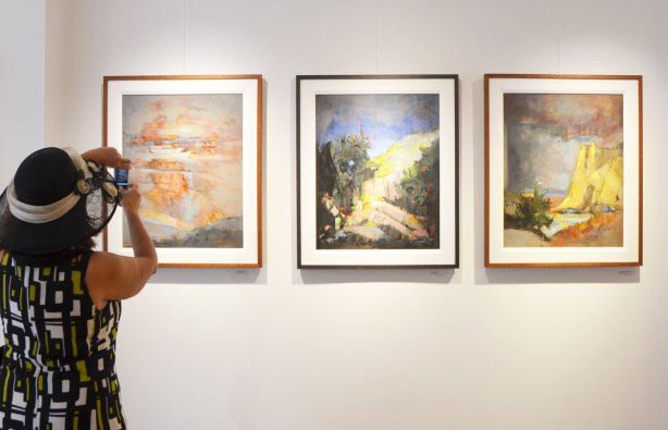 a woman in a floppy black hat is taking pictures of three paintings hanging on a gallery wall.