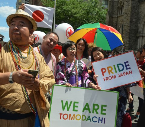 "a group at a parade, rainbow umbrella, one woman holds a sign that says ""Pride from Japen"" and another woman holds a placard that says ""we are tomodachi"""