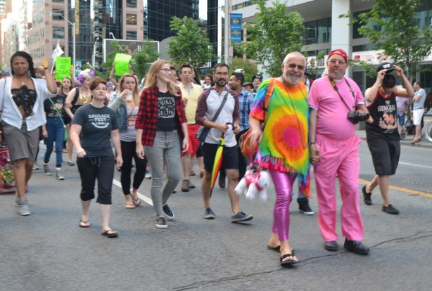 people walking in a parade on Bloor street in Toronto including a man dressed all in pink and a man with shiny magenta leggings and a rainbow tie dyed top
