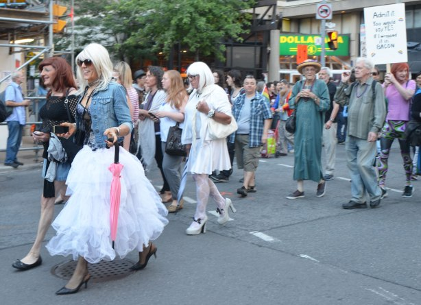 people walking in a parade including a woman in a jean jacket and a frilly white skirt and a person dressed in white dress, hat and high heel shoes.