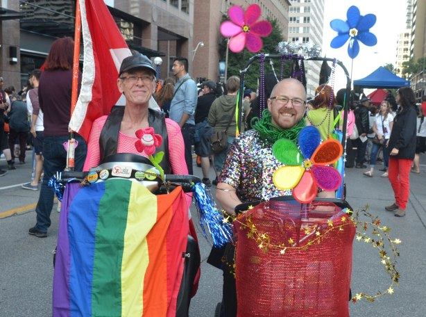two older guys dressed up for trans parade, one in a glittery top and the other in a pink fishnet top, both in motorized scooters, one with a rainbow flag draped over the scooter, the other with big plastic flowers.