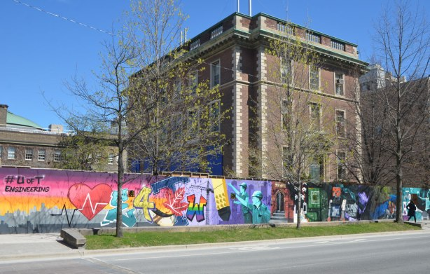 part of a mural on an artwall on hoardings around a construction site for a new engineering building at the University of Toronto, older building behind, long stretch of the mural in the picture