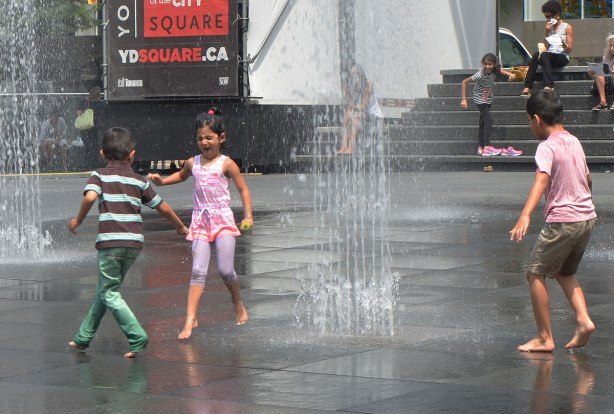 young children play in the fountains at dundas square