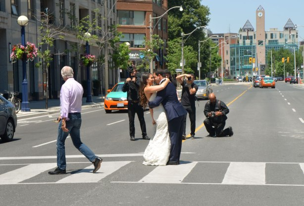 a photo shoot on Bay St., downtown Toronto. The bride and groom are kissing on the crosswalk in the middle of the intersection. People turning to look.