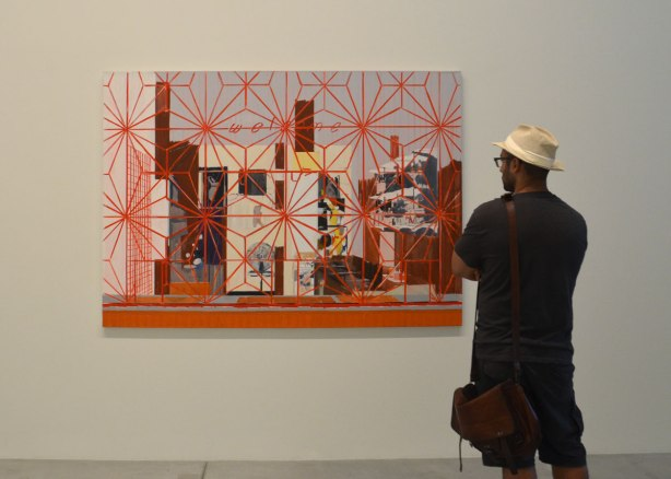 a man in a straw fedora stands in front of a painting called Welcome: Carib by Hurvin anderson, it features a red star patterned grille over the painting, over the window that is in front of the interior scene.