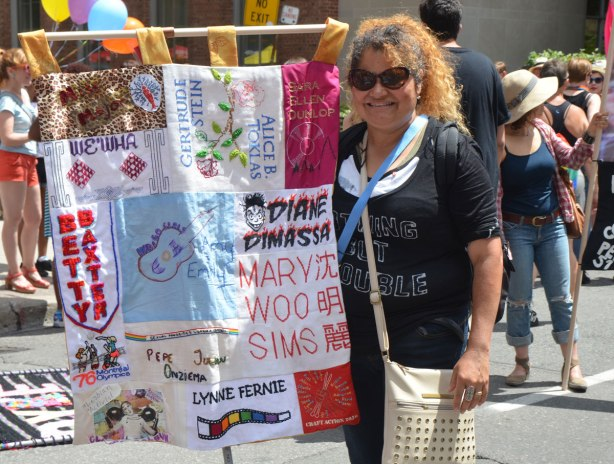 a woman in dark sunglasses stands beside a banner with sections for different famous lesbian women - Mary Woo Sims, Lynne Fernie, Betty Baxter, We Wha, Gertrude Stein,