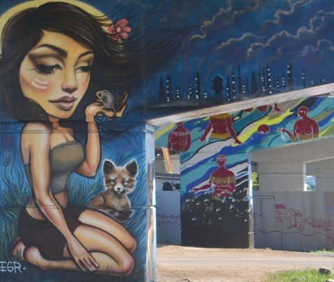 woman holding a mouse in a mural on a bent in the foreground, with another bent in the background, a mural of water and topless red women walking or standing in the water