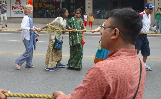 two women in sarees are pulling on a large rope in a parade. In the foreground, a man is pulling on another rope.
