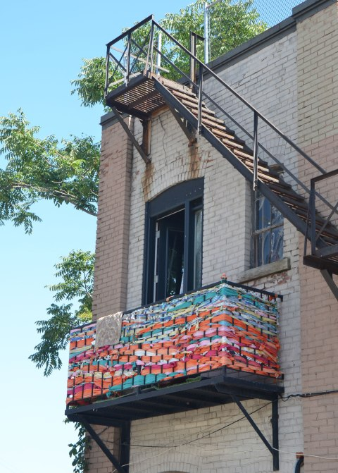 a balcony railing has been decorated with different colours of fabric that has woven between the rails