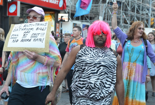a man in a zebra striped dress and a bright pink wig, in a parade, another man is beside him holding a sign that says US anti-trans bathroom bills are full of shit, no more hate