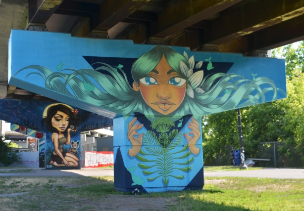 concrete support, or bent, under a ramp has been painted with a mural based on a woman's head coming through a large dark blue triangle