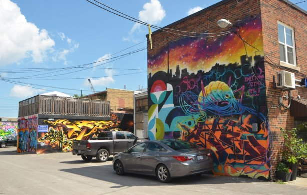 an alley with street art murals, a pickup truck and a car parked in front of one of the murals