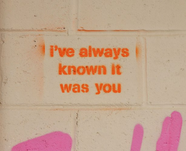 on a concrete wall painted beige, a stencil in orange that says I've always known it was you