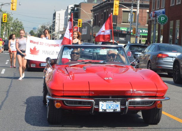 Two men in a red convertible sports car driving slowly down Woodbine Ave in a parade