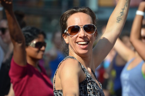 A smiling woman outside, with sunglasses on, in a crowd of people