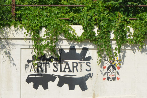logo of two black gears side by side with the words Art Starts written across the middle of them. a small graffiti painting of a girl's head with a heart above it