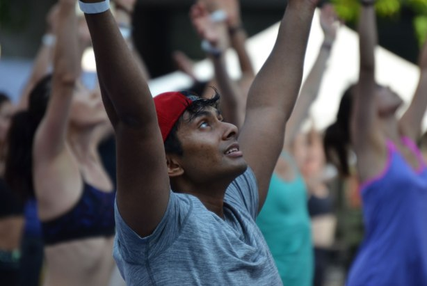 a young Asian man with his arms up in the air, doing yoga positions, with a large group of people