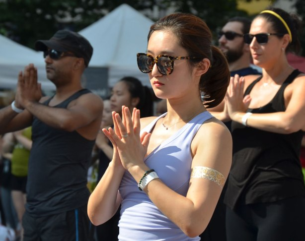 a young Asian woman with big sunglasses, palms together and fingers spread, doing yoga with a group of people outdoors