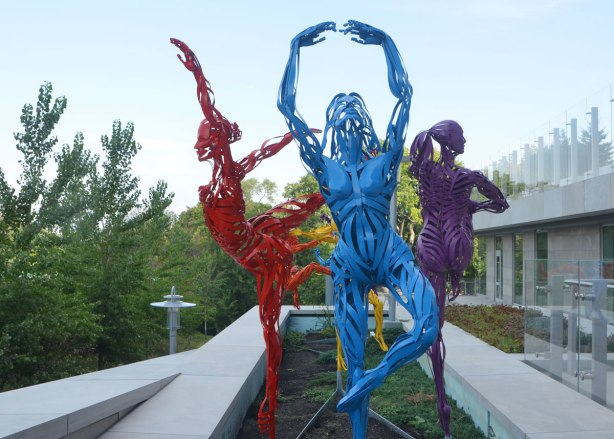 sculptures of three figures in ballet poses, one in blue metal, one in red metal and one in purple. Dancing in a garden outdoors