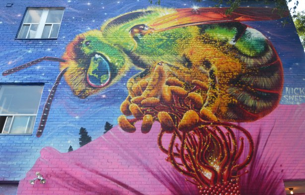 part of a mural, a large colourful bee covered with pollen, sits or flies in the middle of a big pink flower with pollen covered stamens